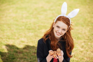 Portrait of a cheerful smiling girl with long ginger hair and bunny ears showing painted easter eggs