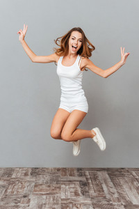 Portrait of a cheerful woman jumping isolated on a gray background