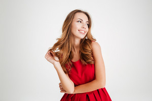 Portrait of a cheerful young brunette woman in red santa claus dress posing and looking away over white background