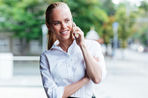Portrait of a cheerful young businesswoman with mobile phone talking outdoors