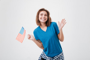 Portrait of a cheerful young woman holding USA flag and looking at camera isolated on a white background