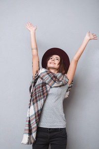 Portrait of a cheerful young woman in hat and scarf standing with raised hands isolated on the gray background