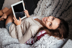 Portrait of a cheerful young woman looking at camera while lying on couch with tablet