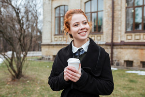 Portrait of a cheerful young woman student with coffee cup standing at the campus