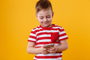 Portrait of a clever young boy typing message on mobile phone isolated over orange background