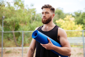 Portrait of a concentrated bearded sports man holding yoga mat outdoors