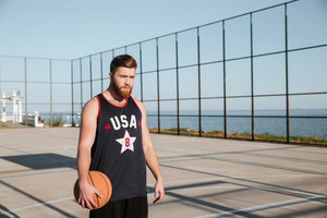Portrait of a concentrated bearded sportsman holding basketball while standing on playground