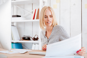 Portrait of a concentrated blonde woman looking through documents while sitting at workplace