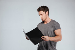 Portrait of a concentrated casual man holding folder over white background