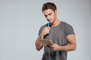 Portrait of a concentrated casual man holding notebook and pen over white background