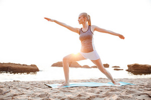 Portrait of a concentrated young woman standing in yoga pose on beach