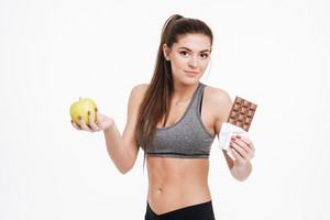 Portrait of a confused fitness woman holding chocolate in one hand and apple in the other, looking at camera isolated on a white background