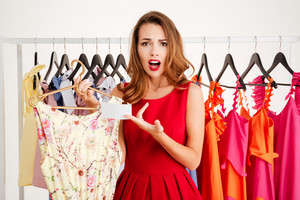 Portrait of a confused lovely woman in red dress choosing what to wear isolated on a white background
