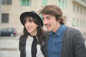 Portrait of a couple of young caucasian man and woman walking trough the streets of the city hugging and smiling looking right - carefreeness, friendship, love, youth concept