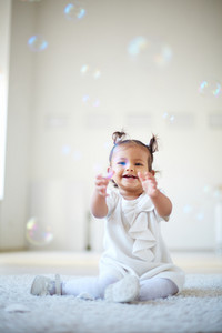 Portrait of a cute little girl having fun with soap bubbles
