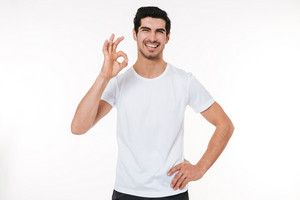 Portrait of a fitness man showing okay sign isolated on a white background