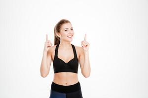 Portrait of a fitness woman pointing fingers up isolated on a white background