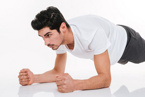 Portrait of a focused handsome young sportsman doing plank exercise over white background
