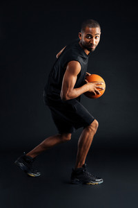 Portrait of a focused young african sports man playing in basketball isolated on a black background