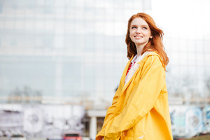 Portrait of a friendly pretty red hair girl in coat standing and posing outdoors