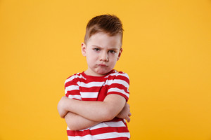 Portrait of a frowning upset little boy looking at camera isolated over orange background