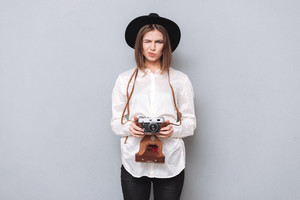 Portrait of a funny frustrated girl in hat standing and holding retro camera isolated on a gray background