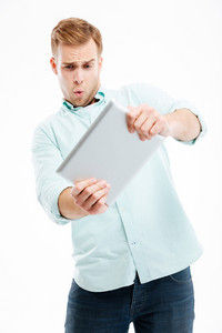 Portrait of a funny redhead man using tablet computer isolated on a white background