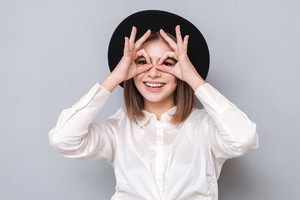 Portrait of a funny young girl in hat looking at camera through fingers isolated on a gray background