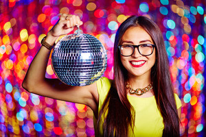 Portrait of a girl in glasses holding disco ball