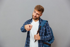 Portrait of a handsome bearded man with backpack pointing finger at camera and winking isolated on a gray background
