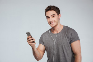 Portrait of a handsome casual man with earphones holding mobile phone isolated on the white background