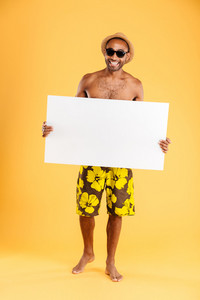 Portrait of a happy afro american man holding blank board and showing okay sign isolated on a orange background