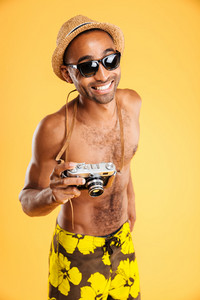 Portrait of a happy afro american man holding retro photo camera isolated on a orange background