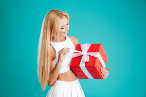 Portrait of a happy blonde girl opening red gift box isolated on the blue background