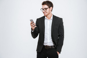 Portrait of a happy businessman in eyeglasses using smartphone over white background