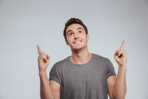 Portrait of a happy casual man pointing fingers up isolated on a white background