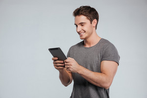 Portrait of a happy casual man using tablet computer over white background