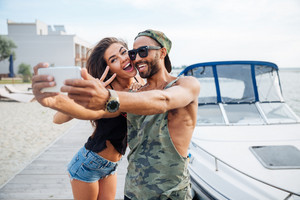 Portrait of a happy couple making selfie photo on smartphone outdoors at the sea pier