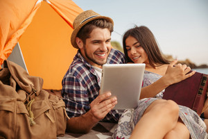 Portrait of a happy couple sitting at the tent using tablet computer and reading book