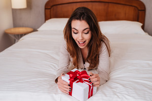 Portrait of a happy excited woman opening present while lying in bed