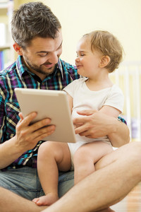 Portrait of a happy father and his little daughter using digital tablet at home