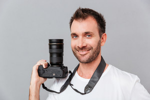 Portrait of a happy handsome man holding camera isolated on a gray background