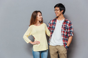 Portrait of a happy interracial couple looking at each other isolated on the gray background