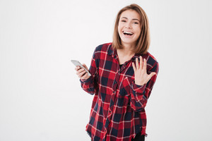 Portrait of a happy laughing woman in plaid shirt holding mobile phone isolated on the white background