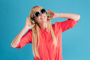 Portrait of a happy pretty young woman listening music with headphones over blue background