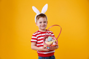 Portrait of a happy satisfied little kid wearing bunny ears and holding easter basket full of colorful eggs isolated over orange background