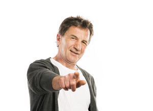 Portrait of a happy senior man pointing to the camera isolated on white background