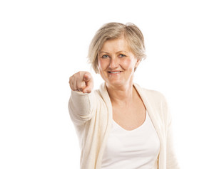 Portrait of a happy senior woman pointing to the camera, isolated on a white background