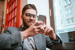 Portrait of a happy smiling businessman in eyeglasses using smartphone while sitting at the office