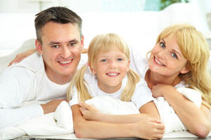 Portrait of a happy smiling family of three dressed in white